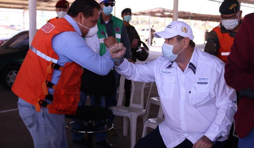 El presidente Alejandro Giammattei (sentado), saluda a Juan Fernano López, alcalde de Quetzaltenango, durante su visita por los trabajos del nuevo hospital para atender pacientes con COVID-19. (Foto: Carlos Ventura)