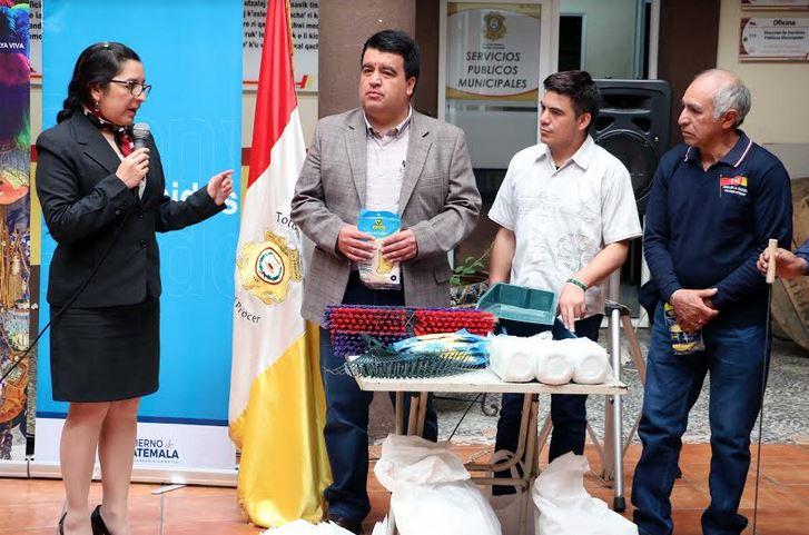 El alcalde -saco gris- recibe insumos de limpieza por parte de la delegada del Inguat, Patricia Rabanales.
