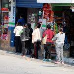 Varias personas caminan por la 11 calle de la zona 1 de Quetzaltenango en busca de abastecerse de alimentos en las tiendas. (Foto: Carlos Ventura)