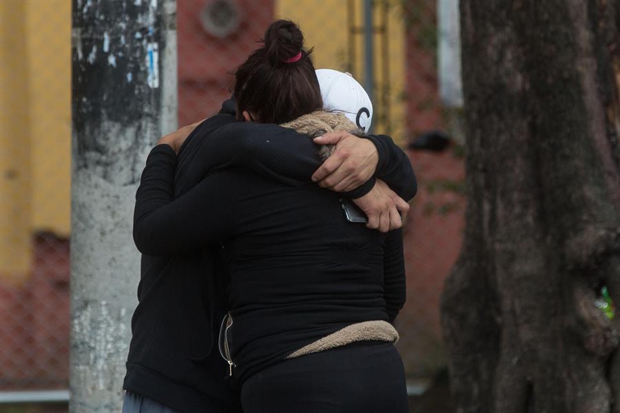 Dos familiares se abrazan a las afueras del cementerio La Verbena, donde fue enterrado un familiar fallecido por COVID-19. (Foto: EFE)
