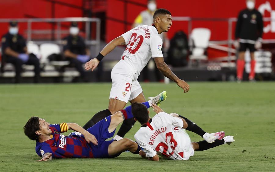 Lionel Messi del Barcelona cae al suelo junto a Sergio Reguilón, defensa del Sevilla, en el duelo que terminó 0-0 en el Ramón Sánchez Pizjuán. (Foto: EFE)