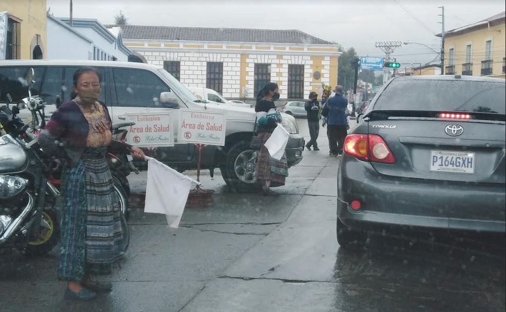 Mujeres con banderas blancas se observan en sobre la 14 avenida de la zona 1 de Xela en busca de ayuda. El desempleo ha crecido en Quetzaltenango debido al COVID-19 y de la población activa solo el 20% se encuentra en actividades. (Foto: Carlos Ventura)
