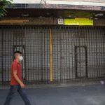 Un joven camina frente a un negocio cerrado por la pandemia en Antigua Guatemala