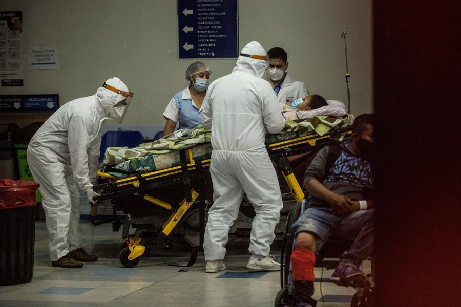 Paramédicos con equipo de protección para evitar el contagio de coronavirus ingresan a una mujer al área de emergencias del Hospital San Juan de Dios, en Ciudad de Guatemala