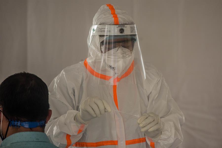 Fotografía de un miembro del personal de Salud preparándose para realizar la prueba del coronavirus en Ciudad de Guatemala