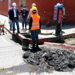 Una cantidad de lodo y basura es sacada en un tragante en la zona 3 de Quetzaltenango, el cual es observado por el alcalde Juan Fernando López, de casco blanco. (Foto: Carlos Ventura)