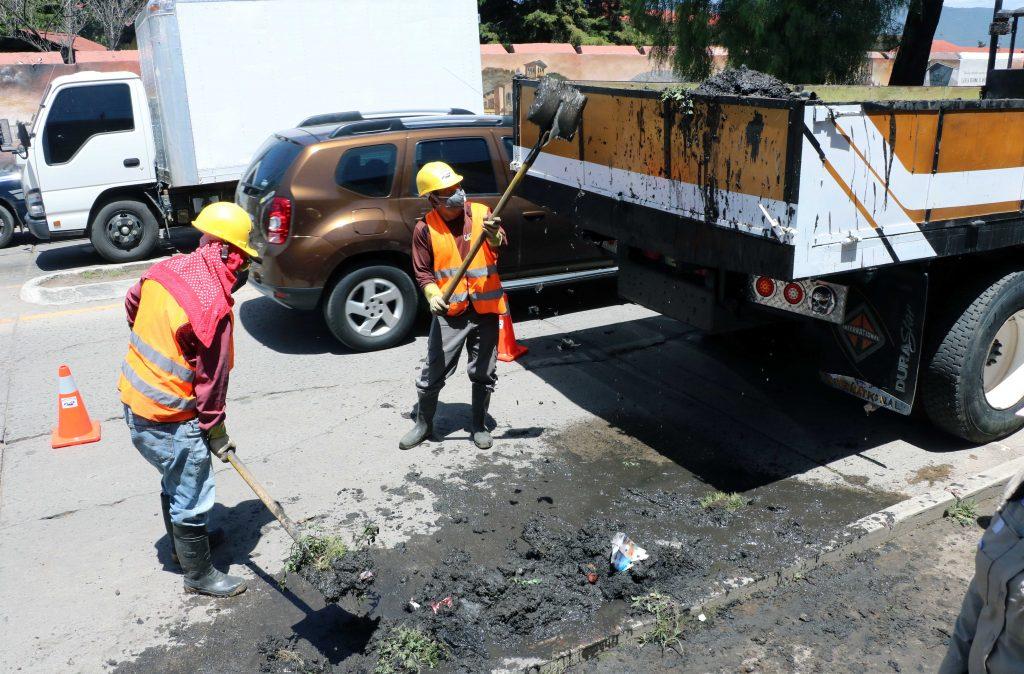Trabajadores de una empresa contratada para la limpieza de tragantes trasladan lodo y basura hacia un camión, luego de sacarlo del desagüe en la zona 3 de Xela. (Foto: Carlos Ventura)