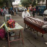 Dos empleados funerarios trasladan el féretro de una víctima de coronavirus, quien murió en la emergencia del Hospital Nacional San Juan de Dios, y será enterrado en el cementerio La Verbena, en Ciudad de Guatemala