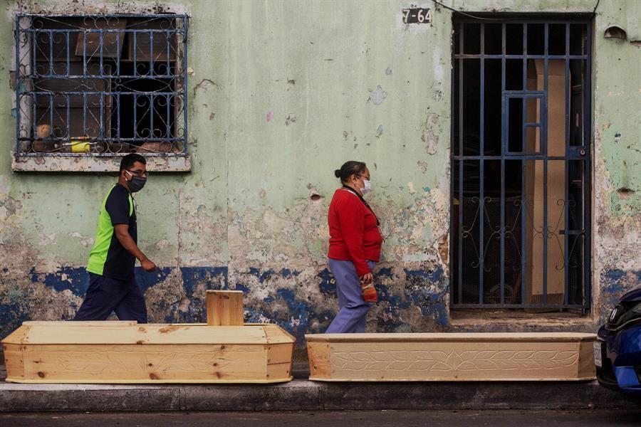 Personas pasan frente a féretros de la fábrica Estrada, el 6 de julio del 2020, en ciudad de Guatemala (Guatemala). EFE/Esteban Biba/Archivo