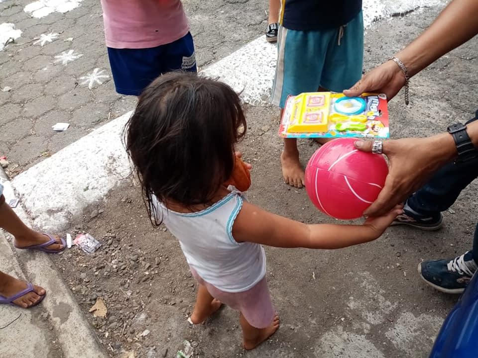 Una pequeña niña recibe juguetes por parte de uno de los voluntarios. (Foto: Cristian Soto)
